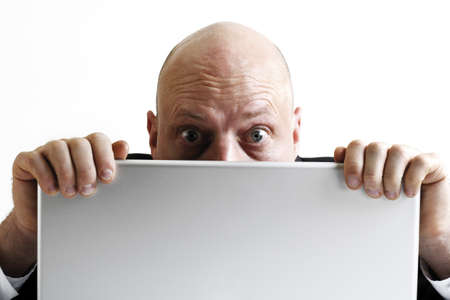 fearing: Man hiding behind lap top, close-up