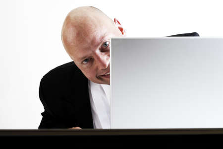mirthful: Man looking from behind lap top, smiling LANG_EVOIMAGES
