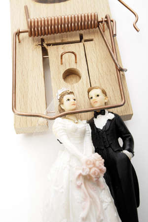 confiding: Wedding couple figurines lying in mouse trap, close-up