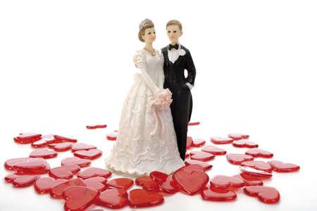 빨간 하트의 중간에 서있는 웨딩 커플 인형