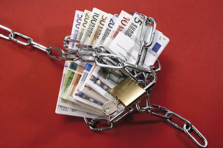 land locked: Bunches of Euro banknotes in chains LANG_EVOIMAGES