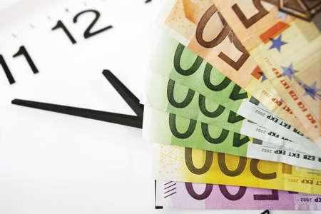 billets euros: Les billets en euros et horloge, symbole pour le temps c'est de l'argent