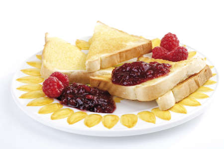 Sliced bread and rasberry jam on plate