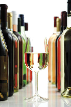 conformance: Glass of white wine between wine bottles, close-up