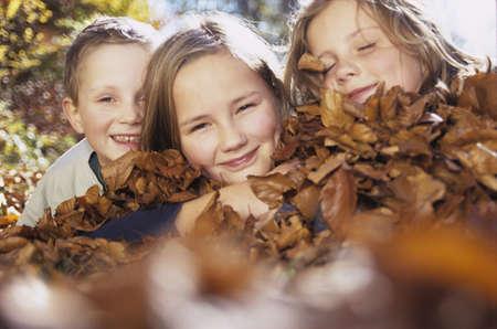 proximity: Children (4-13) lying on autumn leaves