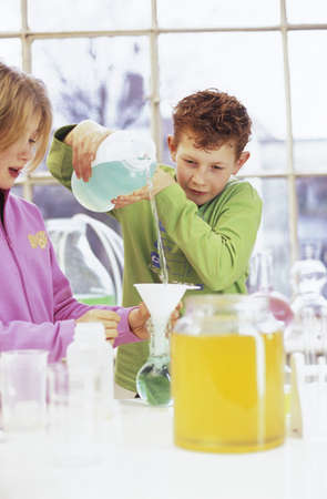 enquiring: Boy and girl (8-11) in chemical lab, boy pouring liquid
