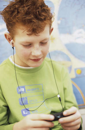 chellange: Boy (10-11) listening to MP3 player