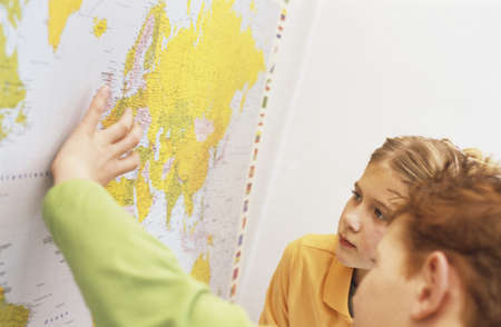 chellange: Boy and girl (6-9) looking at world map, elevated view
