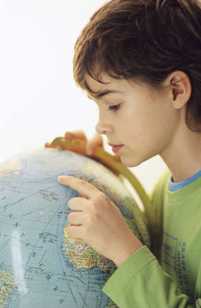 chellange: Boy (10-11) looking at globe, side view