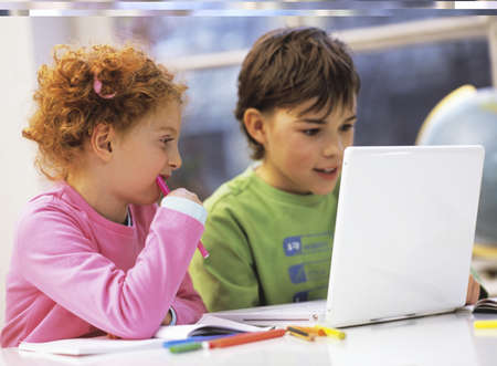 enquiring: Boy and girl (6-9) using laptop