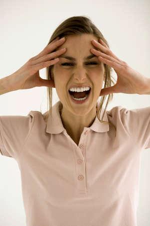 faccia disperata: Giovane donna con la testa fra le mani, gridando, close-up