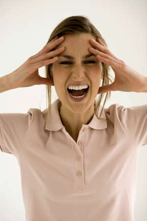 Young woman with head in hands, shouting, close-up LANG_EVOIMAGES