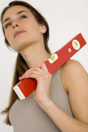 aplomb: Young woman holding red spirit level looking away, close-up