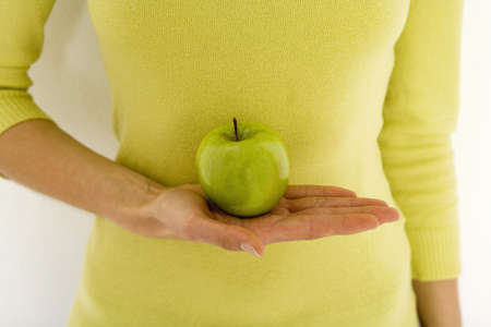gratified: Woman holding green apple LANG_EVOIMAGES