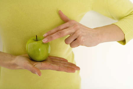 gratify: Young woman holding apple, mid section, close-up LANG_EVOIMAGES