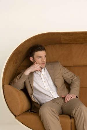 aplomb: Businessman sitting on sofa, looking away