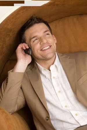 aplomb: Man sitting on sofa using mobile phone, smiling