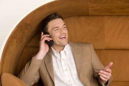 aplomb: Man sitting on sofa using mobile phone, laughing