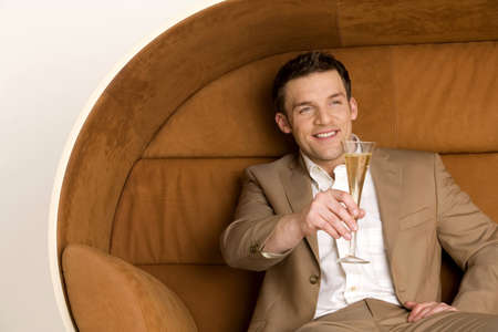 aplomb: Man sitting on sofa holding out champagne glass, smiling