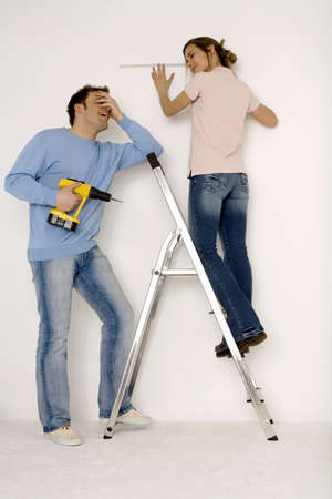 perplexing: Young couple, man holding electric drill, woman measuring wall with scale LANG_EVOIMAGES