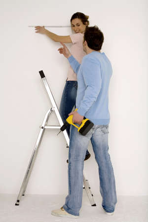 furnish: Young couple, man holding electric drill, woman measuring wall with scale LANG_EVOIMAGES