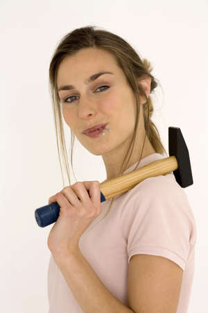 hope indoors luck: Young woman holding hammer, close-up, portrait LANG_EVOIMAGES