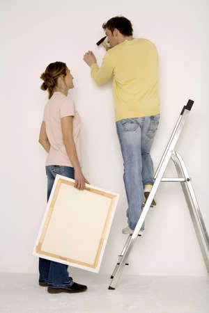 hang body: Young couple hanging up painting, man standing on ladder LANG_EVOIMAGES