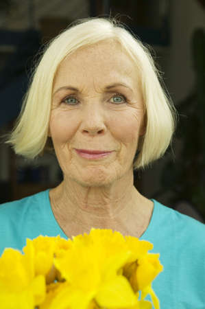 mirthful: Senior woman with flowers, close-up, portrait