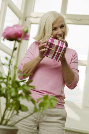 mirthful: Senior woman holding gift box, smiling, low angle view LANG_EVOIMAGES