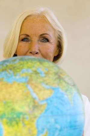 clothes interesting: Senior woman holding globe, portrait, close-up LANG_EVOIMAGES