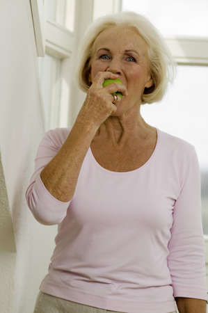 hope indoors luck: Senior woman eating fruit, portrait