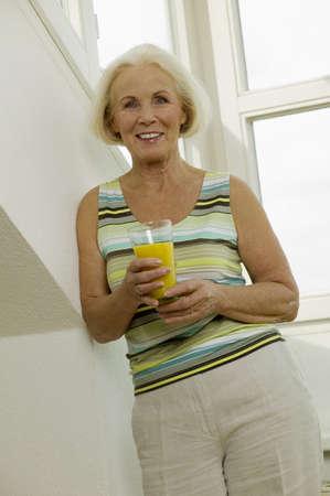 kind hearted: Senior woman holding glass of juice, smiling, portrait LANG_EVOIMAGES