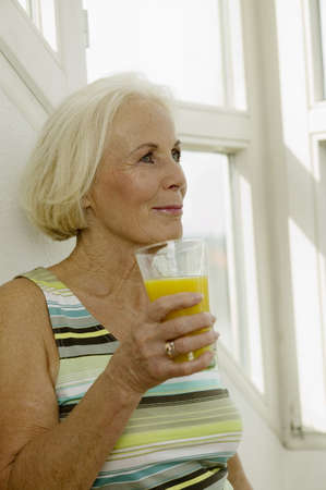 kind hearted: Senior woman holding glass of juice, smiling, close-up LANG_EVOIMAGES
