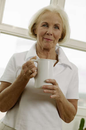 kind hearted: Senior woman holding jug, low angle view, portrait
