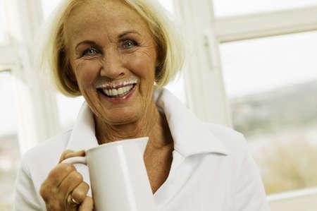 kind hearted: Senior woman holding milk jug, smiling, portrait, close-up LANG_EVOIMAGES