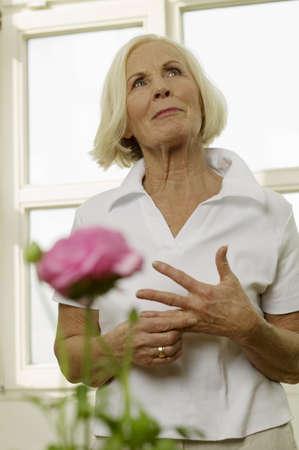 gratify: Senior woman standing, looking up, portrait