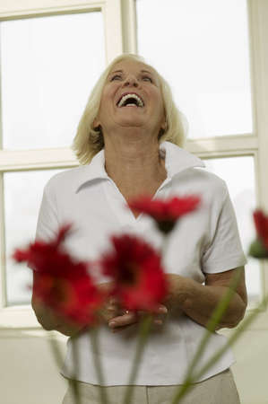 contented: Senior woman laughing, looking up, portrait