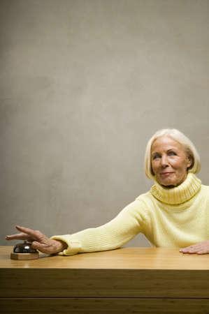 aplomb: Senior woman ringing bell, smiling LANG_EVOIMAGES