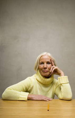 mirthful: Elder lady sitting at desk with pencil LANG_EVOIMAGES