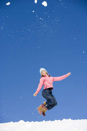 unworried: Austria, girl (10-11) jumping in snow, low angle view