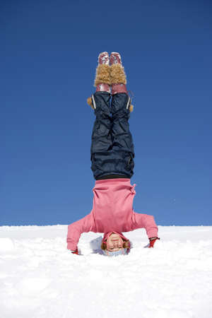 headstand: Austria, girl (10-11) doing headstand in snow