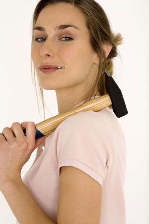 aplomb: Woman holding hammer with nail in mouth, portrait, close-up