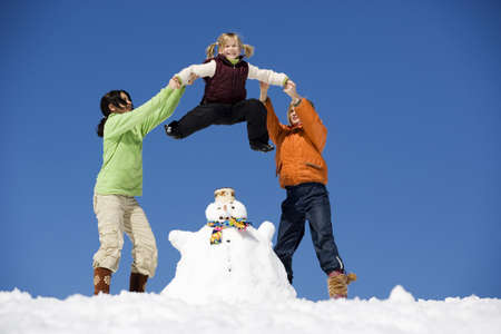 12 13 years: Austria, girls (6-17) with snowman, low angle view LANG_EVOIMAGES