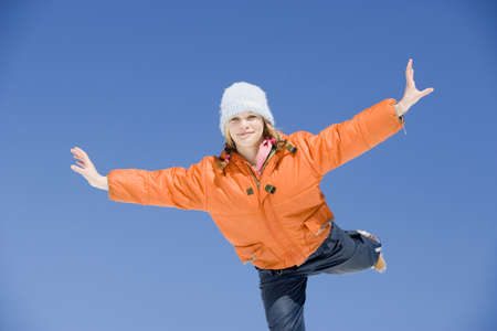 unworried: Austria, girl (12-13) balancing on one leg with arms outstretched, smiling, portrait