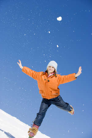 unworried: Austria, girl (12-13) in snow balancing on one leg with arms outstretched, smiling, portrait