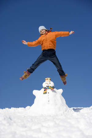 jubilation: Austria, girl (12-13) jumping on snowman, smiling, low angle view