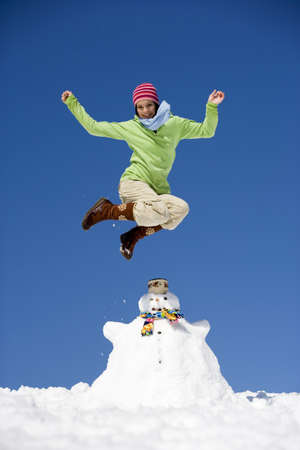fascination: Austria, teenage girl (16-17) jumping on snowman, smiling, low angle view