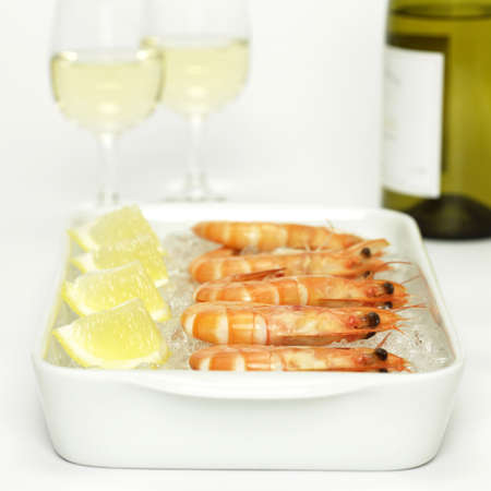 citrons: Prawns with lemon slices on crushed ice and white wine, close-up