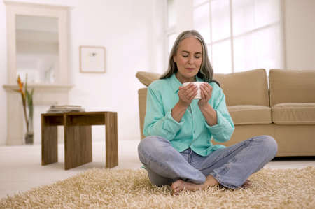 gentle dream vacation: Mature woman holding cup of tea, eyes closed