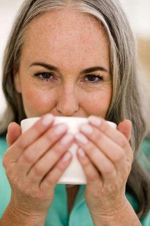 gentle dream vacation: Mature woman drinking tea, portrait, close-up